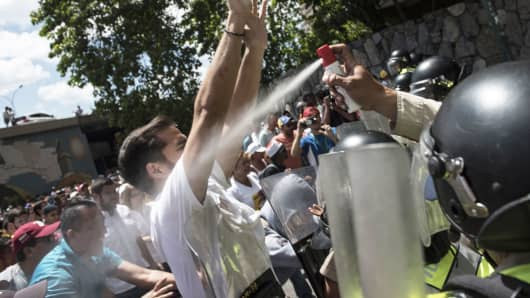 A National Guard officer discharges pepper spray on demonstrators during a second day of protests as the Supreme Court reverses its decision to seize the powers of the opposition-led Congress in Caracas, Venezuela, on Saturday, April 1, 2017.