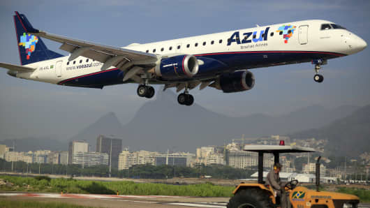 A worker mows grass while an Azul SA jet lands at the the Santos Dumont Airport (VCP) in Rio de Janeiro, Brazil.