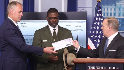 White House press secretary Sean Spicer (R) gives Interior Secretary Ryan Zinke (L) the first quarter check of US President Donald Trump's salary which he donated to the National Park Service as Tyrone Brandyburg (C), Harpers Ferry National Historical Park Superindendant, looks on during the daily press briefing at the White House in Washington, DC, on April 3, 2017.