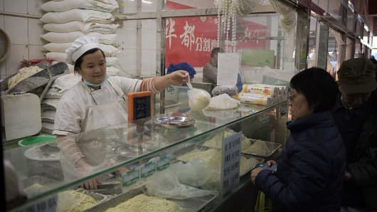 In this picture taken on November 2, 2016, a woman buys fresh noodles at a market in Beijing.