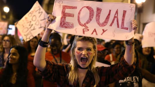 Clarissa Horsfall holds a sign reading, 'Equal Pay,' as she joins with others during 'A Day Without A Woman' demonstration on March 8, 2017 in Miami, United States.