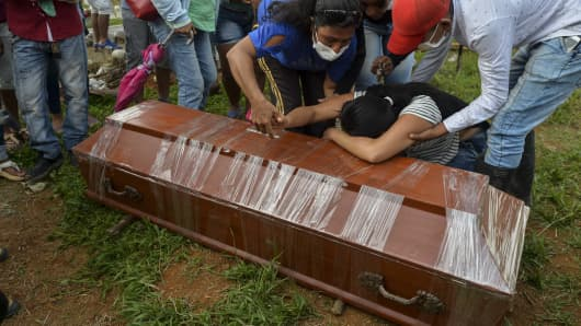 A woman cries over the coffin of a relative killed in the mudslides caused by heavy rains, at the cemetery in Mocoa, Putumayo department, Colombia on April 3, 2017.