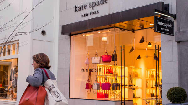 A pedestrian walks past a Kate Spade store in Corte Madera, California.