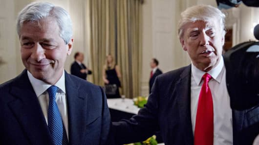 In this 2017 file photo, President Donald Trump stands next to Jamie Dimon, chief executive officer of JPMorgan Chase & Co., left, in the State Dining Room of the White House in Washington.
