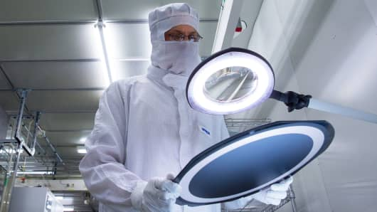 An employee inspects a wafer at the Infineon Technologies AG microchip and sensor manufacturing facility in Regensburg, Germany. Shares of the company are up 15 percent in 2017.