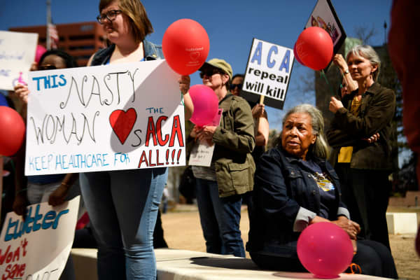 People listen during a protest to save the Affordable Care Act last month in Denver.