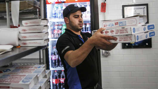 An employee carries an order for a customer at a Domino's Pizza restaurant in Detroit.