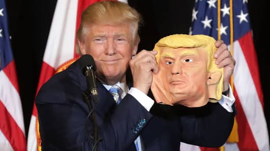 Republican presidential nominee Donald Trump holds up a rubber mask of himself.