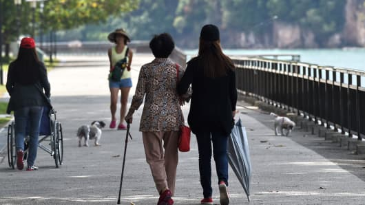 A care-taker walks with an elder woman in a park in Singapore.