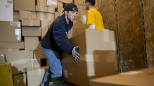Package handlers unload boxes from a trailer to be sorted for final delivery at a FedEx Corp