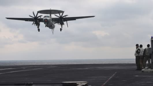 U.S. Navy crew members look at an E-2C Hawkeye as it lands on the deck of the Nimitz-class aircraft carrier USS Carl Vinson during a South Korea-U.S. joint military exercise in seas east of the Korean Peninsula on March 14, 2017.