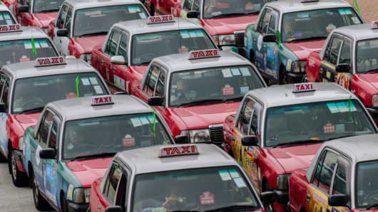 Taxi drivers sit in their parked cars as they take part in a protest on a road near the government offices in Hong Kong on March 17, 2017.