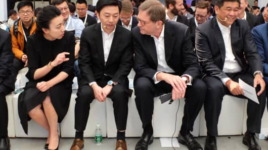 Jochem Heizmann, (2nd R) Volkswagen China CEO, talks with Zhifei Li (2nd L), Mobvoi CEO and co-founder Yuanyuan Li (L), before a news conference announcing the strategic partnership between the two companies in Beijing, April 6, 2017.
