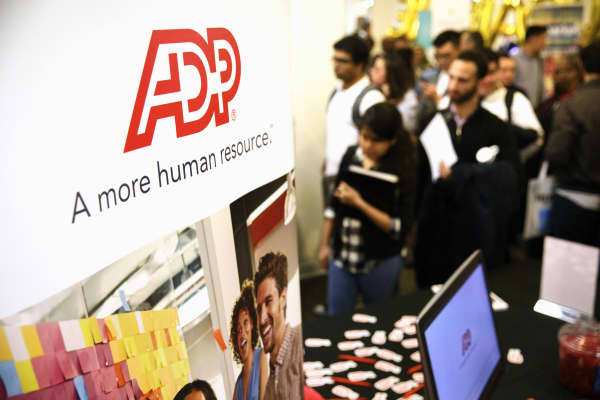 ADP LLC signage is displayed as job seekers wait in line during the TechFair LA job fair in Los Angeles, California.