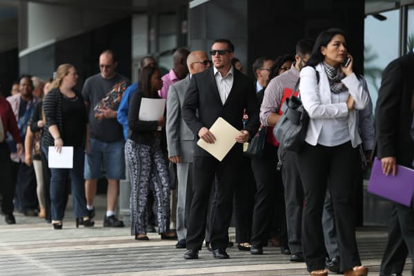 Job seekers wait to get into the JobNewsUSA job fair at the BB&T Center in Sunrise, Florida.