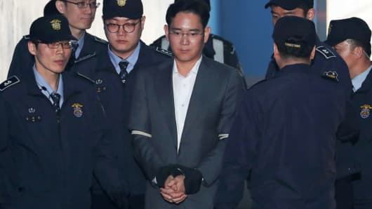 Jay Y. Lee, co-vice chairman of Samsung Electronics Co., center, is escorted by prison officers as he arrives at the Seoul Central District Court in Seoul, South Korea, on Friday, April 7, 2017.