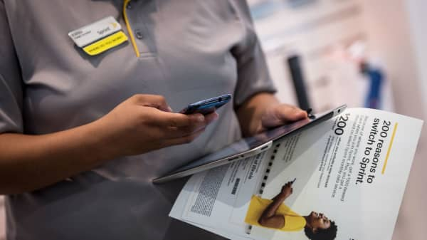 A Sprint employee uses a smartphone and Apple iPad at the company's store in Chicago.
