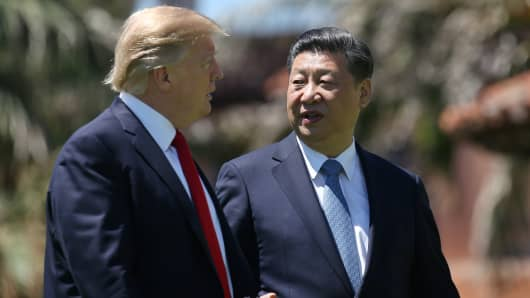 President Donald Trump and China's President Xi Jinping chat as they walk along the front patio of the Mar-a-Lago estate after a bilateral meeting in Palm Beach, Florida, U.S., April 7, 2017.