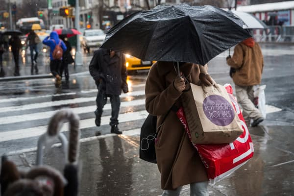 People walk along the sidewalk in the rain on Christmas Eve on December 24, 2014 in New York City.