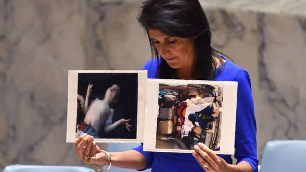 US Ambassador to the UN, Nikki Haley holds photos of victims as she speaks as the UN Security Council meets in an emergency session at the UN on April 5, 2017, about the suspected deadly chemical attack that killed civilians, including children, in Syria.