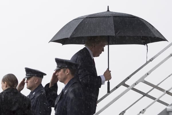 President Donald Trump (3rd R) boards Air Force One under heavy rain at Andrews Air Force Base, Maryland, April 6, 2017.