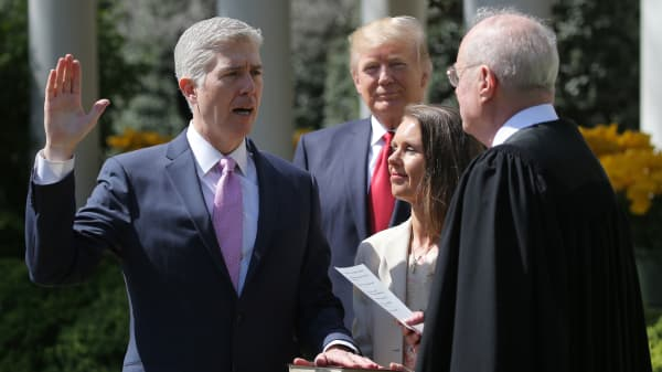 Judge Neil Gorsuch (L) is sworn in as an associate justice of the Supreme Court by Supreme Court Associate Justice Anthony Kennedy (R) , as U.S. President Donald J. Trump (C) watches with Louise Gorsuch in the Rose Garden of the White House in Washington, U.S., April 10, 2017.