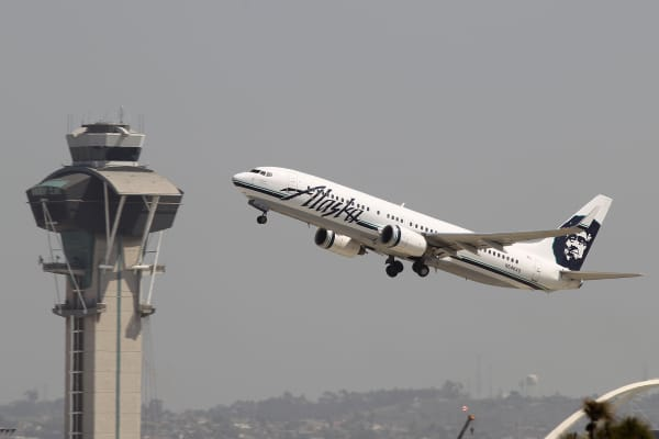 An Alaska Airlines jet passes the air traffic control tower at Los Angles International Airport (LAX) during take-off in Los Angeles, California.