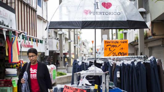 A pedestrian walks past a merchandise rack in the Rio Piedras neighborhood in San Juan, Puerto Rico.