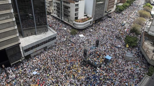 Thousands of demonstrators protesting against President Nicolas Maduro's government march in Caracas on April 8, 2017. The opposition is accusing pro-Maduro Supreme Court judges of attempting an internal 'coup d'etat' for attempting to take over the opposition-majority legislature's powers last week.