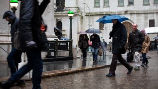 People carry umbrellas while walking along Wall Street in front of the New York Stock Exchange (NYSE) in New York.