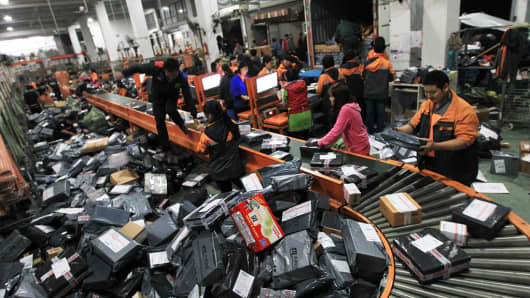 Staff of STO Express sort packages for delivery on November 12, 2015 in Wenzhou, Zhejiang Province of China.