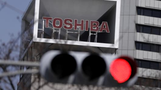 Signage for Toshiba is displayed atop the company's headquarters as a red traffic light stands illuminated in Tokyo.