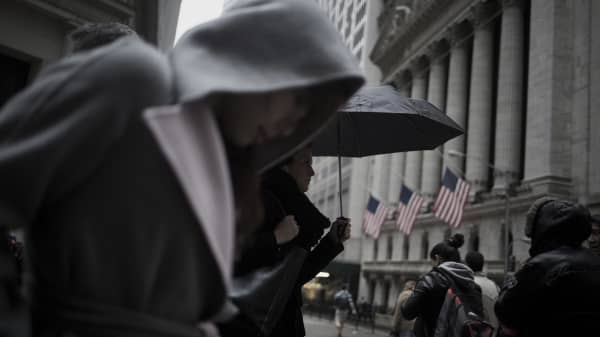 A woman carrying an umbrella walks past the New York Stock Exchange (NYSE) in New York.
