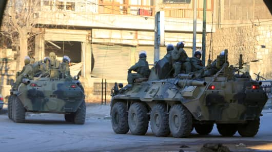 Russian soldiers, on armoured vehicles, patrol a street in Aleppo, February 2017.