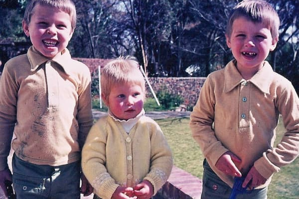 Elon (Left) and Kimbal (Right) flank their younger sister Tosca, now a filmmaker, in a childhood photo outside their home in South Africa.