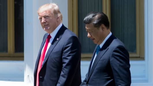 U.S. President Donald Trump (L) and Chinese President Xi Jinping walk together at the Mar-a-Lago estate in West Palm Beach, Florida, April 7, 2017.
