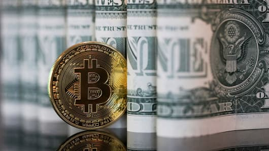 A bitcoin token stands next to a collection of U.S. one dollar bills in this arranged photograph in London, U.K., on Wednesday, Jan. 4, 2017.