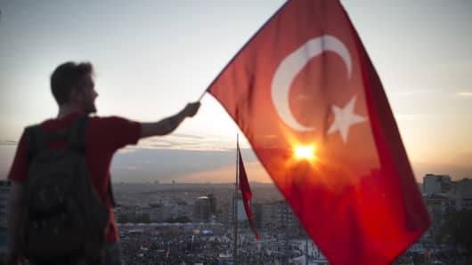 A man holding a Turkish flag.