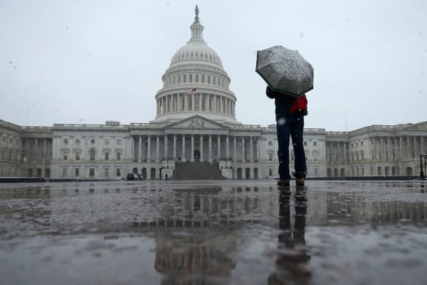 A person takes cover under an umbrella while snapping a photo of the U.S. Capitol in Washington, DC.