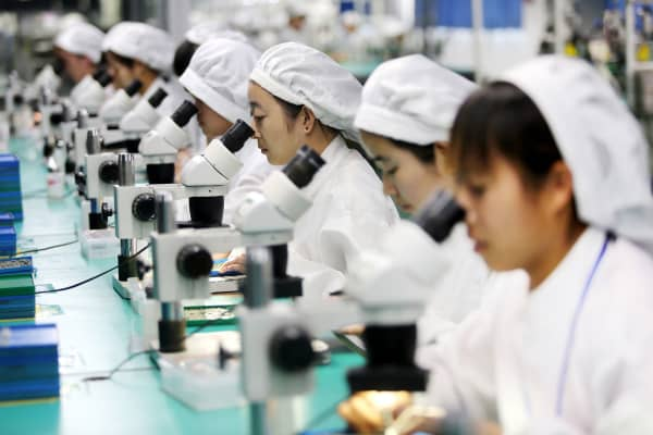 Chinese employees working on micro and special motors for mobile phones at a factory in Huaibei, China.