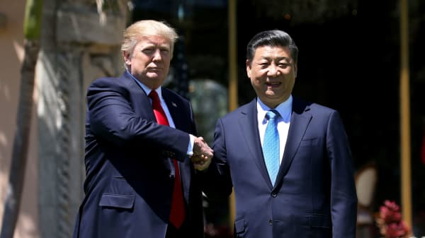 President Donald Trump (L) and China's President Xi Jinping shake hands while walking at Mar-a-Lago estate after a bilateral meeting in Palm Beach, Florida, April 7, 2017.