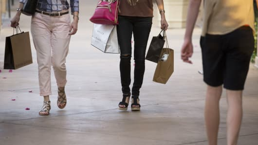 Shoppers carry bags while walking through the Scottsdale Quarter shopping mall in Scottsdale, Arizona.