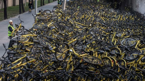 A worker from the bike share company Ofo puts a damaged bike on a pile at a makeshift repair depot.