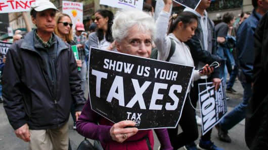 Protestors take part in the 'Tax March' calling on President Donald Trump to release his tax records on April 15, 2017 in New York.