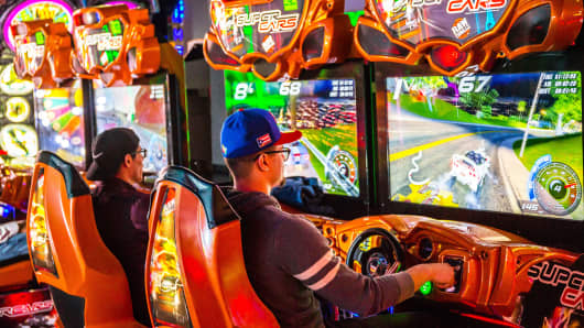Customers play a car racing arcade game at a Dave & Buster's Entertainment location.