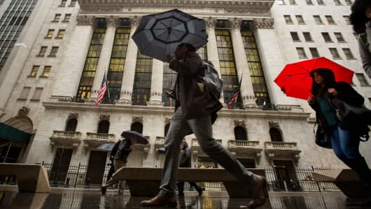 Pedestrians with umbrellas pass in front of the New York Stock Exchange