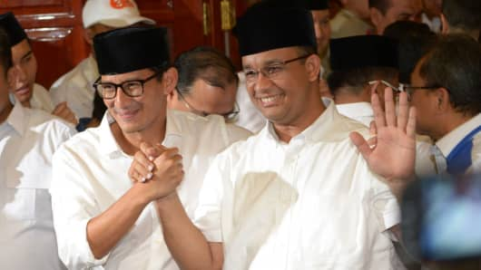 Jakarta governor-elect Anis Baswedan (R) and his deputy governor-elect Sandiaga Una (L) hold hands during a press conference in Jakarta on April 19, 2017.
