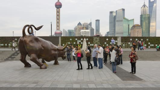 Tourists watching the bull statue in front of the Stock Exchange on the Bund, Pudong skyline in the distance, Shanghai, China.