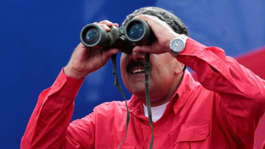 Venezuela's President Nicolas Maduro uses binoculars during a rally in Caracas, Venezuela April 19, 2017.
