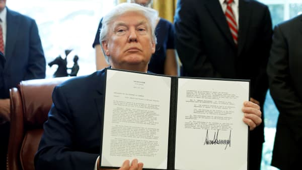 President Donald Trump holds up a directive ordering an investigation into the impact of foreign steel on the American economy after signing it in the Oval Office of the White House in Washington, April 20, 2017.